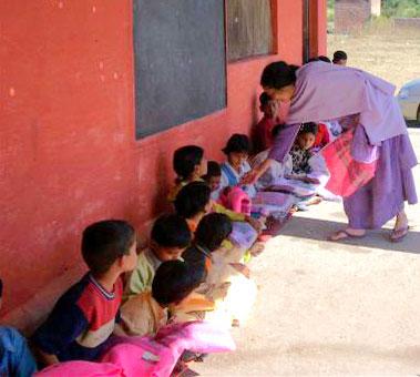 Mataji distributing food and shawls to poor children of a school near Rishikesh